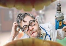 De gekke tandarts arts kijkt in mond en houdt boor Royalty-vrije Stock Foto