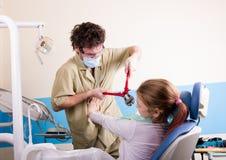 De gekke tandarts behandelt tanden van de ongelukkige patiënt De patiënt is angst aangejaagd royalty-vrije stock foto's