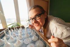 De gekke vrouwelijke wetenschapper of de student zijn in zijn laboratorium stock afbeelding