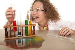 De gekke vrouwenwetenschapper met reageerbuizen grijpt rood Royalty-vrije Stock Foto