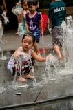 De geklede kinderen spelen bij waterfontein Stock Fotografie