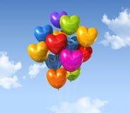 De gekleurde ballons van de hartvorm op een blauwe hemel stock illustratie
