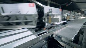 De gekleurde document dekking wordt in bijlage aan industriële machine terwijl zich het bewegen stock video