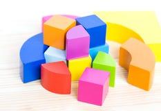 De gekleurde houten blokken, kubussen, bouwen op een lichte houten achtergrond voort Stock Foto's