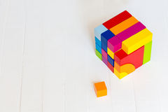 De gekleurde houten blokken, kubussen, bouwen op een lichte houten achtergrond voort Een kubus van gekleurde houten details Stock Fotografie