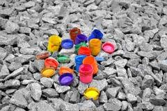 De gekleurde kleine verfblikken liggen op een grijze kiezelsteen Stock Foto