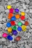 De gekleurde kleine verfblikken liggen op een grijze kiezelsteen Stock Fotografie