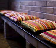 De gekleurde kussens liggen op een rij op een bank dichtbij de bakstenen muur Royalty-vrije Stock Foto's