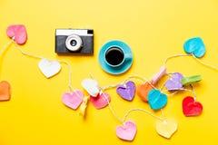 De gekleurde lichten van de hartvorm en kop van koffie met camera Stock Afbeeldingen