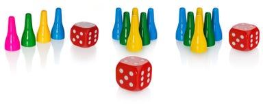 De gekleurde panden en het rood dobbelen Vastgestelde stukken in de gele kleuren, groen, blauw Kubus in rood met witte ogen Royalty-vrije Stock Afbeelding
