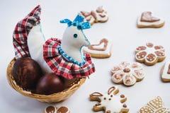 De gekleurde stuk speelgoed kip en de geschilderde die kippenpaaseieren in een rijs nestelen en peperkoekkoekjes, met wit en choc royalty-vrije stock afbeeldingen