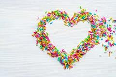 De gekleurde suiker bestrooit in hartvorm op witte houten lijst stock fotografie