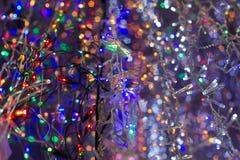 De gekleurde verschillende slingers die van lichtenkerstmis op een rij winkel hangen Royalty-vrije Stock Fotografie