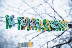 De gekleurde wasknijpers op de drooglijn zijn behandeld met vorst in de winter stock foto's