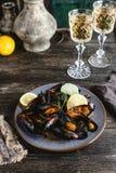 De gekookte mosselen met shells dienden op plaat met twee glazen witte wijn Stock Foto's