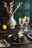 De gekookte mosselen met shells dienden op plaat met twee glazen witte wijn stock foto