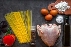 De gekookte Noedels van de Spaghetti Ongekookte spaghetti en ruwe kip aan boord Ingrediënten voor de eigengemaakte eieren van de  Stock Afbeeldingen