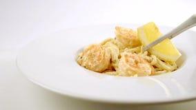 De gekookte spaghettideegwaren met een garnaal op een wit plateren het verfraaien met een citroen stock footage