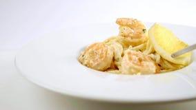 De gekookte spaghettideegwaren met een garnaal op een wit plateren het verfraaien met een citroen stock videobeelden