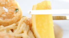 De gekookte spaghettideegwaren met een garnaal op een wit plateren het verfraaien met een citroen stock video