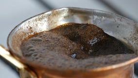 De gekookte weg zwarte koffie van de vluchtelingsgrond in een koper Turk op wit gasfornuis stock footage