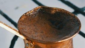De gekookte weg zwarte koffie van de vluchtelingsgrond in een koper Turk op wit gasfornuis stock video