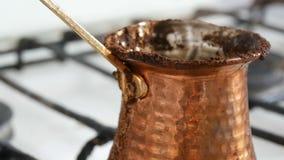 De gekookte weg zwarte koffie van de vluchtelingsgrond in een koper Turk op wit gasfornuis stock videobeelden