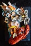 De gekookte zeekreeft, de verse oesters, de garnalen, de mosselen en de tweekleppige schelpdieren dienden in zwarte steenplaat royalty-vrije stock afbeelding