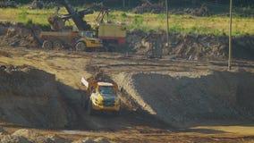 De geladen mijnstortplaatsvrachtwagen verlaat de heuvel stock videobeelden