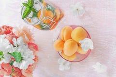 De gele abrikozen in een transparante vaas met een ontgiftende drank maakten van munt en abrikoos op de achtergrond met boeket va stock foto's