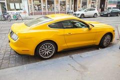 De gele auto van Ford Mustang 2015, zijaanzicht Stock Foto