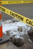 De gele Band van de Voorzichtigheid over een gat in de grond Stock Afbeeldingen