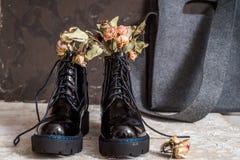 De gele bloemen groeien in de oude zwarte laarzen want origineel verfraai stock foto's