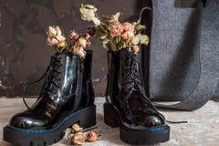 De gele bloemen groeien in de oude zwarte laarzen want origineel verfraai stock afbeeldingen
