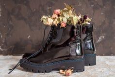 De gele bloemen groeien in de oude zwarte laarzen want origineel verfraai royalty-vrije stock afbeelding