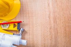De gele bouwvakker rolde het witte rood van het blauwdrukkenniveau Stock Afbeelding