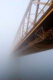 De gele brug verdwijnt in de dikke de herfstmist Twee groepen van drie vogels vliegen van de brug in verschillende richtingen Stock Foto