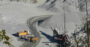De gele bulldozer laadt graniet in een geel lichaam van de stortplaatsvrachtwagen, die proces in een steengroeve werken, steengro stock videobeelden