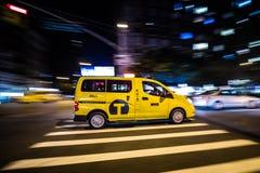 De Gele Cabine die van NYC snel bij Nacht in Manhattan, New York overgaan Royalty-vrije Stock Afbeeldingen