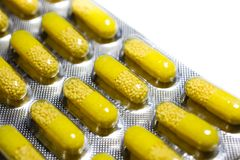 De gele capsules met gele korrelsgeneeskunde in de grijze blaar van de tabletpil pakken macrodiedetail in op witte achtergrond wo royalty-vrije stock afbeeldingen