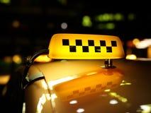 De gele controleur van het taxiteken bij nacht stock foto