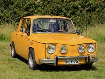 De gele die Auto van Renault 8S op Gras wordt geparkeerd Stock Fotografie