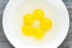 De gele dooier van kwartelseieren in witte porseleinkom close-up Royalty-vrije Stock Afbeeldingen