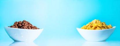 De gele en chocoladevlokken in witte platen vormen op een blauw close-up tot een kom als achtergrond Grote grote fotogrootte Tril Stock Afbeelding