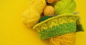 De gele en groene lagen van wol liggen op de lijst De favoriete hobby breit royalty-vrije stock foto's