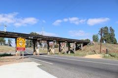 De gele en zwarte Lage Ontruiming, Overheight-Voertuigen moet teken bij een lage brug van de houtschraag tegenhouden royalty-vrije stock foto