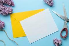 De gele envelop en de spatie voor tekst en sering bloeien op een heldere in lichtblauwe achtergrond Hoogste mening royalty-vrije stock afbeeldingen