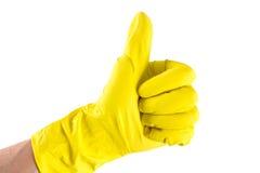 De gele handschoen voor het schoonmaken op het wapen van de vrouw toont duimen Stock Fotografie