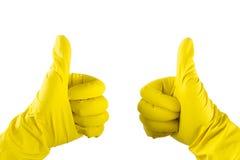 De gele handschoen voor het schoonmaken op het wapen van de vrouw toont duimen Stock Afbeelding