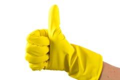 De gele handschoen voor het schoonmaken op het wapen van de vrouw toont duimen Royalty-vrije Stock Afbeelding